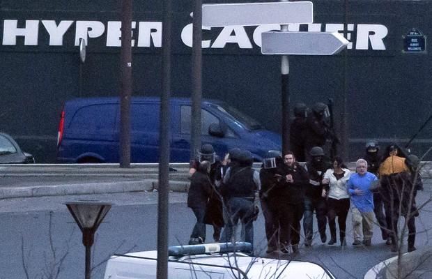 Agentes escoltam reféns liberados em ação policial após horas de sequestro em mercado kosher de Paris (Foto: Michel Euler/AP)