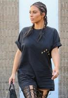 Kim Kardashian surge com penteado exótico e botas de cano altíssimo