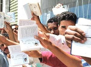 Desempregados brasileiros mostram suas carteiras de trabalho e papéis de seguro-desemprego (Foto: Reprodução Internet)