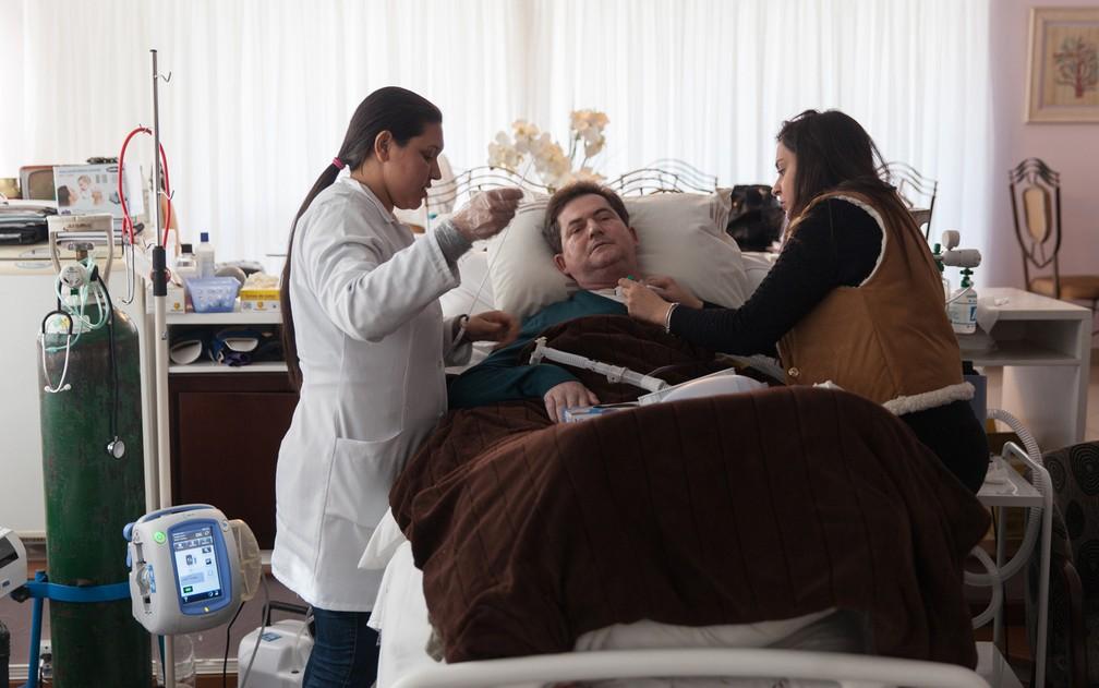 A filha mais velha e uma enfermeira cuidam de Carlos Magon (Foto: Marcelo Brandt/G1)