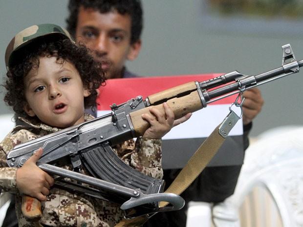 Menino com rifle durante comemorações em Sanaa (Foto: Mohamed al-Sayaghi/Reuters)