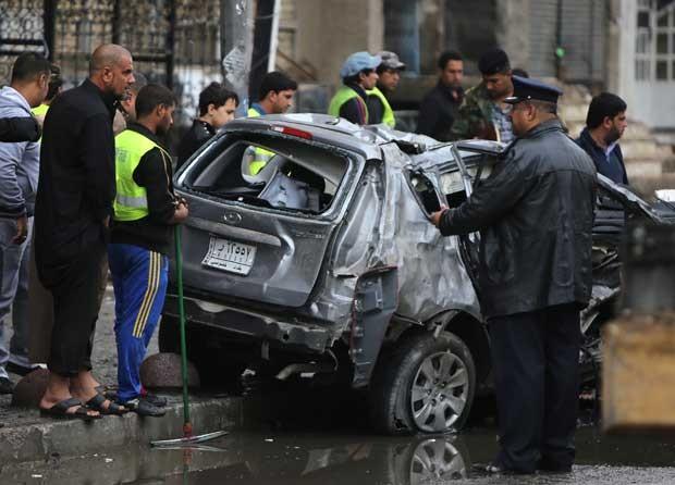 Iraquianos inspecionam o local de um ataque com carro-bomba no bairro de Karrada nesta quarta-feira (20) (Foto: Ahmad al-RUBAYE/ AFP)