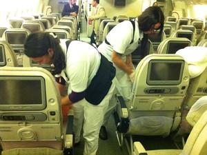 Faxineiras limpam o interior do avião (Foto: Flávia Mantovani/G1)