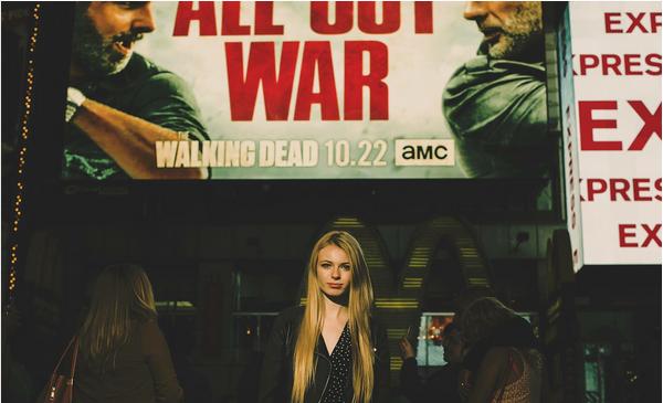 A atriz Addy Miller em frente a um anúncio de The Walking Dead (Foto: Instagram)