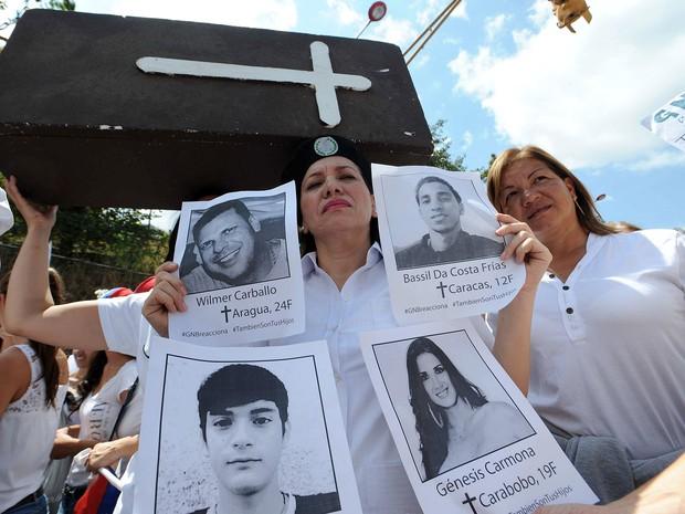 Manifestantes empunham cartazes com os nomes das vítimas em protestos na Venezuela nesta quarta-feira (26). (Foto: Pedro Guzman/AFP)