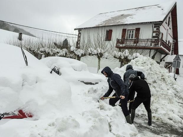 Pessoas removem a neve que cobriu diversos carros na cidade espanhola de El Espinal, na quinta (5) (Foto: AP Photo/Alvaro Barrientos)