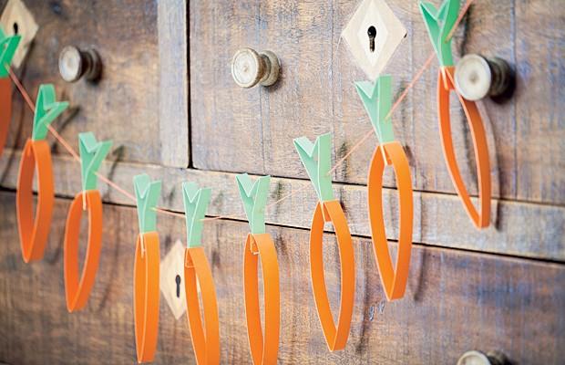Nem só com bandeirinhas os fios podem ser decorados. Aqui, cenouras de papel enfeitam o varal, que alegra o móvel mais rústico. Para fazê-las, basta cortar tiras de papel – se preferir, use um tipo mais grosso – e moldar. Para transformar em varal, passe  (Foto: Elisa Correa/Editora Globo)