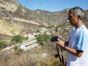 Engenheiro que já viu a sangria do Gargalheiras, agora registra o momento mais crítico da barragem  (Foto: Anderson Barbosa/G1)