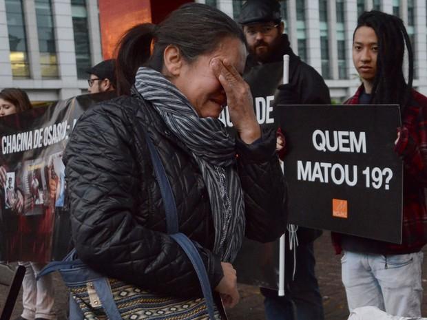Mulher chora durante ato que lembra um ano da chacina em Osasco e Barueri (Foto: J. Duran Machfee/Estadão Conteúdo)
