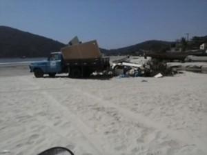 Caminhão descatando lixo na Praia do Perequê, em Guarujá (Foto: Reprodução/VC no G1)