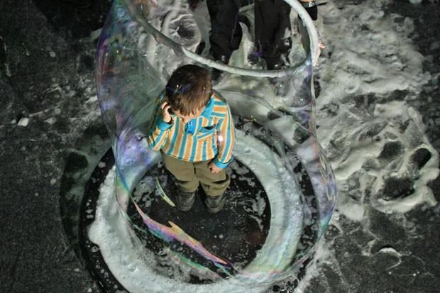 Menino fala ao celular dentro de uma bolha gigante de sabão (Foto: Radek Mica/AFP)