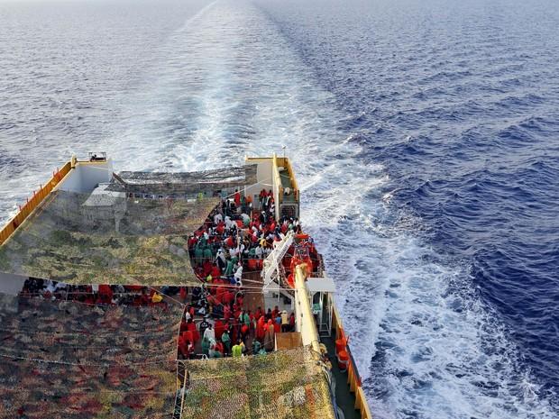 Multidão de migrantes resgatados do Mar Mediterrâneo são levados no navio norueguês Siem Pilot até o porto de Cagliari, na Itália. O navio resgatou centenas de pessoas da água (Foto: Gregorio Borgia/AP)