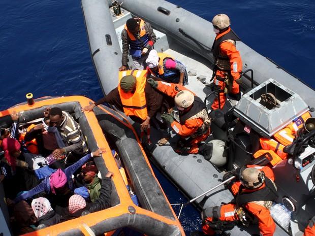Oficiais alemães ajudam imigrantes resgatados perto da ilha de Lampedusa a embarcar na fragata Hessen, na sexta-feira (8) (Foto: Reuters/Bundeswehr/PAO Mittelmeer/Handout via Reuters)
