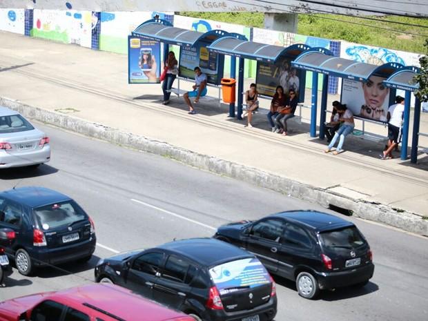 Passageiros aguardam por transporte no ponto de ônibus.  (Foto: Jonathan Lins/G1)
