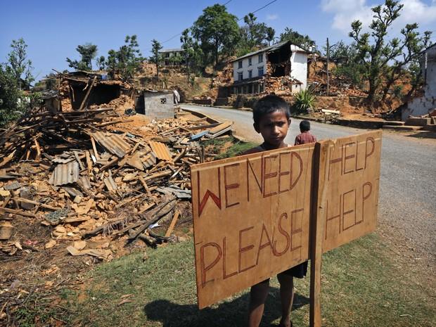 Criança pede ajuda em área devastada por terremoto no Nepal (Foto: AP/ Manish Swarup)
