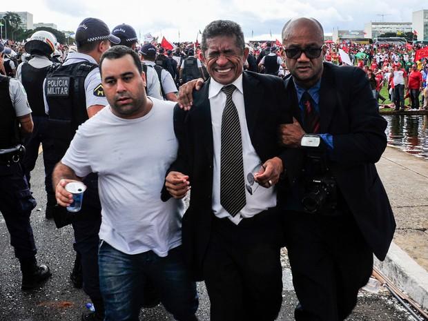 O deputado Vicentinho (PT-SP) é retirado de de confusão durante protesto de Centrais Sindicais no gramado do Congresso Nacional, em Brasília (Foto: Zeca Ribeiro/Câmara dos Deputados)