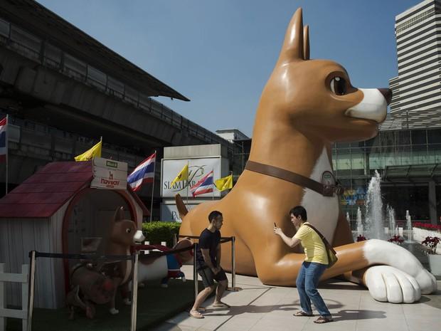 Dupla tira foto perto de estátua de 10 metros de altura com personagem da animação 'Khun Tongdaeng: The inspirations', perto de shopping em Bangcoc (Foto: Nicolas Asfouri/AFP)