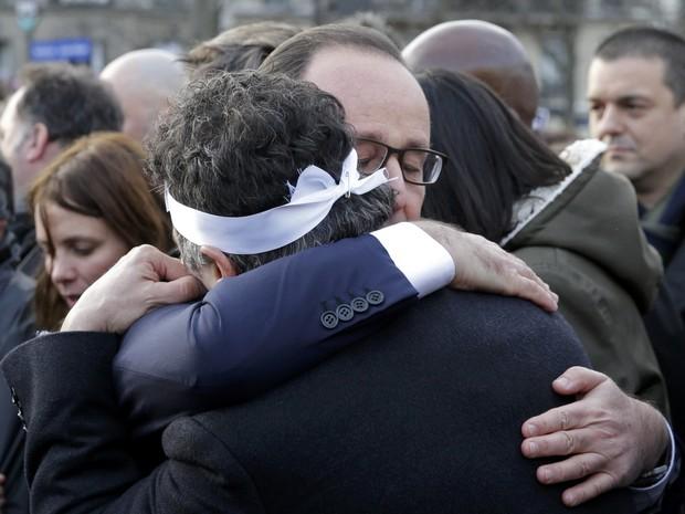 O presidente francês, François Hollande, abraçou durante a marcha o médico Patrick Pelloux, colaborador do Charlie Hebdo que chegou ao jornal pouco depois do ataque à redação (Foto: REUTERS/Philippe Wojazer)