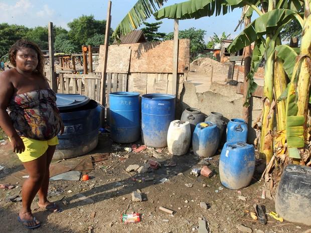 Daniele e sua família tomam banho de roupa no quintal de casa, pois barracos da comunidade não têm banheiro (Foto: Marcos de Paula / G1)