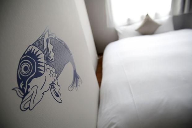 Carpa pintada na parede de um dos hotéis econômicos do Japão; quartos são minúsculos, mas têm decoração moderna e melhor serviço que hotéis-cápsula (Foto: Yuya Shino/Reuters)