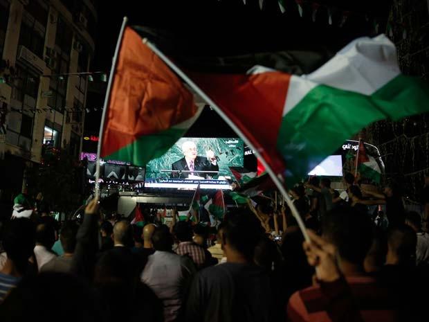 Em Ramallah, palestinos erguem bandeira da Palestina ao assistir a transmissão do discurso de Mahmoud Abbas na Assembleia Geral da ONU (Foto: AFP PHOTO / ABBAS MOMANI)