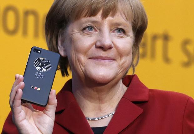 A chanceler da Alemanha, Angela Merkel, mostra um smartphone em feira de telecomunicações em Hannover em 5 de março (Foto: Fabrizio Bensch/Reuters)