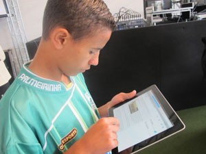 Menino usa internet Wi-Fi em tablet na favela Paraisópolis (Foto: Tatiana Santiago/ G1)