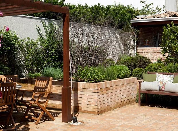 Além de pérgola sobre a mesa e banco para relaxar, este quintal dos sonhos tem uma horta. Projeto assinado pela paisagista Cláudia Munõz (Foto: Edu Castello/Editora Globo)