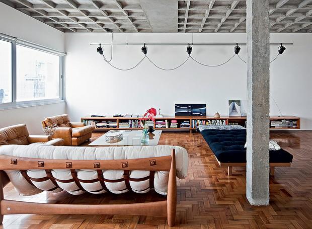 No living impera o brutalismo, com o concreto exposto nas vigas estruturais e na laje nervurada. O ambiente, no entanto, passa calma, graças aos móveis de madeira e couro e às paredes brancas. Projeto do escritório AR Arquitetos (Foto: Maíra Acayaba/Casa e Jardim)
