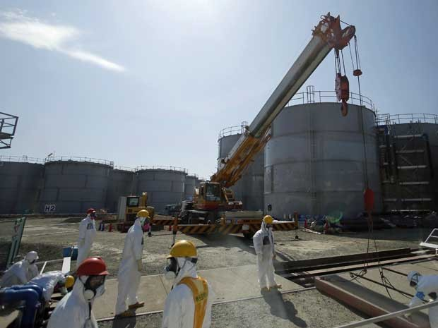 Trabalhadores usam protetor próximo a um tanque da Central Atômica de Fukushima. (Foto: Arquivo / AP Photo)