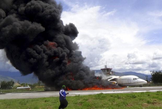 Fogo começou depois que tambor carregado com óleo caiu da aeronave (Foto: AP)