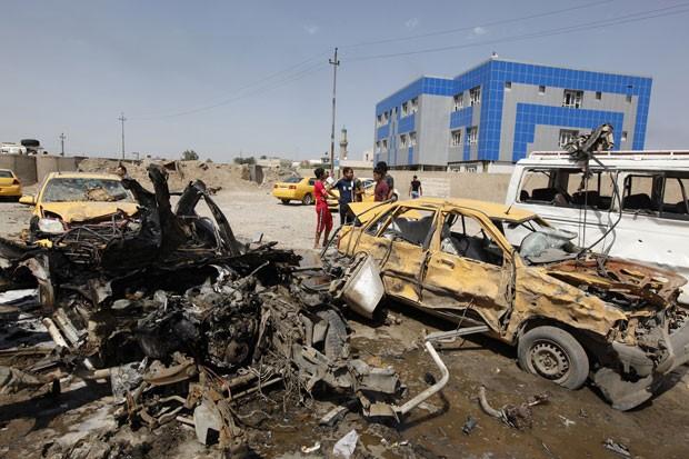 Pessoas se reúnem em local de explosão em Bagdá nesta terça-feira (13). Diversos ataques na capital iraquiana mataram pelo menos 19 pessoas (Foto: Ahmed Saad/Reuters)