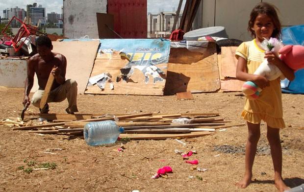 Genival corta madeira para fazer o fogo e dar de comer a família; são 24 dias sob o viaduto  (Foto: Rafael Barbosa/G1)