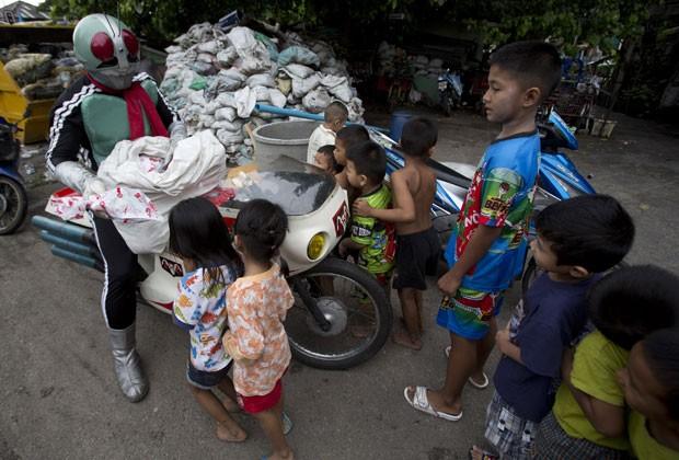 Ele distribuiu brinquedos para crianças carentes de Bangcoc nesta quinta-feira (3) (Foto: Sakchai Lalit/AP)