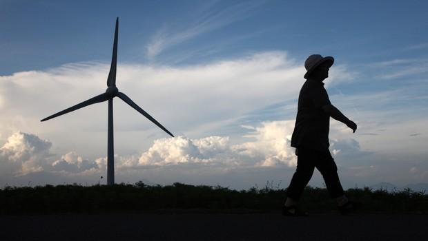 Mulher passa diante de turbina de energia eólica em uma fazenda da Electric Power development Co. (J-Power) em Koriyama, na prefeitura de Fukushima, em agosto de 2012 (Foto: Bloomberg/Getty Images)