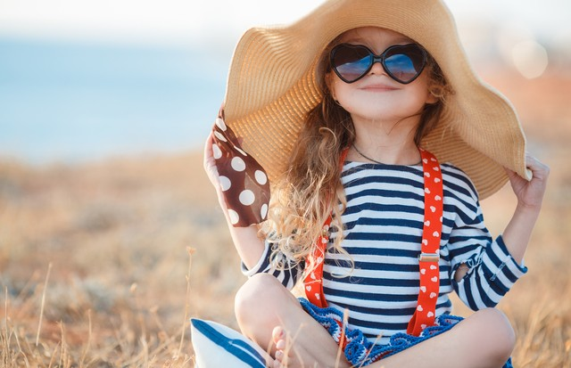 Happy little girl, a brunette with long curly hair, dressed in a striped sailor's t-shirt and red suspenders, wearing dark sun glasses, sitting on a rocky beach in a big straw hat. (Foto: Getty Images/iStockphoto)