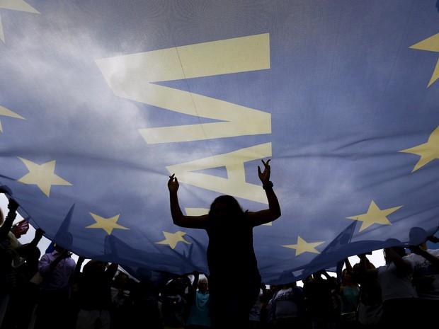 Manifestantes protestam em frente ao Parlamento grego em Atenas nesta terça-feira (30) (Foto: Reuters/Yannis Behrakis)
