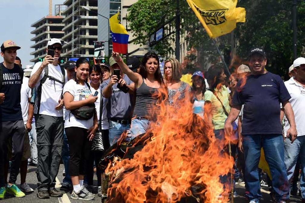 Manifestantes queimam foto do presidente da Venezuela, Nicolás Maduro, durante protesto em Caracas, nesta quarta-feira (19) (Foto: Ronaldo Schemidt / AFP)