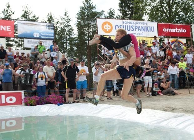 Todo o ano é disputado na Finlândia o 'Campeonato Mundial de Carregamento de Esposas'. Na foto, Taisto Miettinen carrega sua parceira Kristiina Haapanen durante a competição. A dupla foi campeã do campeonato, alcançando a quarta vitória seguida no evento. (Foto: Timo Hartikainen/AFP)