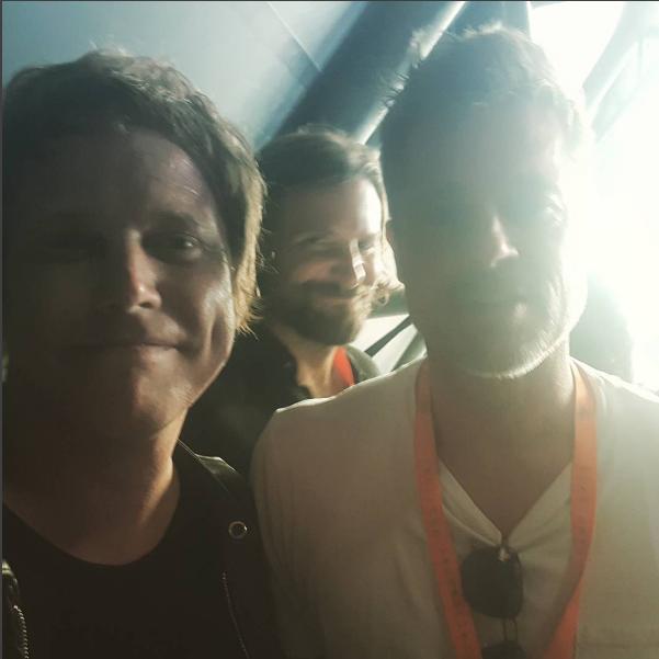 Chris Simmons com Brad Pitt e Bradley Cooper ao fundo (Foto: Reprodução/Instagram)