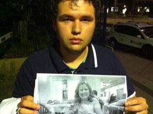 Leonardo Leite Santos mostra uma foto da mãe, Valéria Santos Leite, em frente ao IML Central de São Paulo (Foto: Gabriela Gasparin/G1)