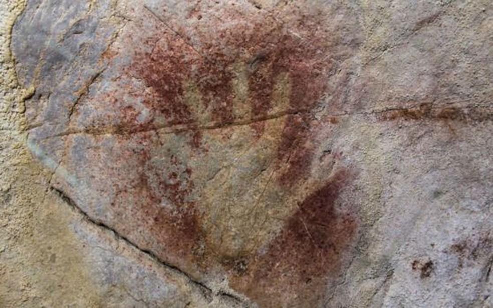 Na parede da gruta El Castillo, na Espanha, o contorno de uma mão feito com tinta vermelha (Foto: BBC/D. von Petzinger)