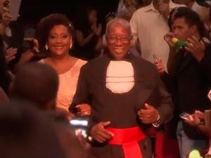 Uma das filhas do idoso o acompanhaou até o palco  (Foto: Reprodução/TV Bahia)