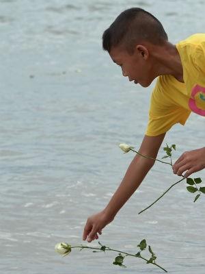Menino Thai coloca uma rosa no mar perto do memorial do tsumani em Ban Nam Khem (Foto: Pornchai Kittiwongsakul/ AFP)