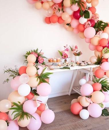 Em vez de usar as bexigas de forma tradicional, crie arcos diferentes que se apoiam nas laterais da mesa. Adicione plantas ao efeite para um arranjo delicado e criativo.  (Foto: Reprodução/Pinterest)