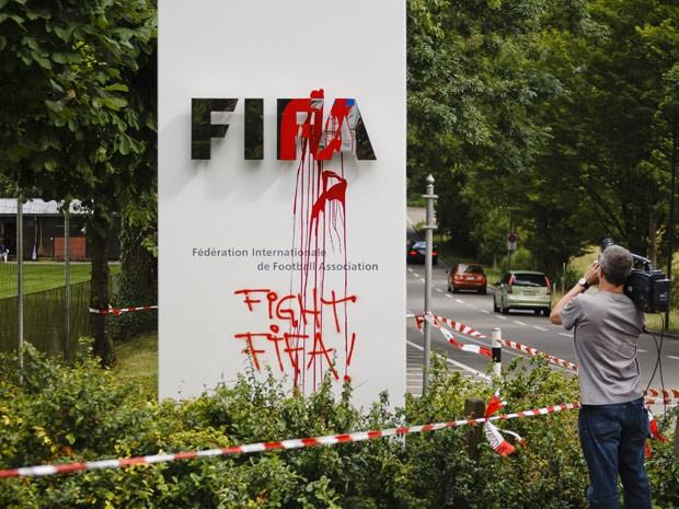 Homem filma o logo da Fifa em frente à orgnização, em Zurique; manifestantes jogaram tinta vermelha na placa (Foto:  AFP Photo/Michael Buholzer)