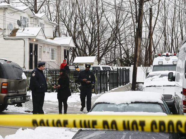 Polícia se reúne em casa no bairro do Queens, em Nova York, onde homem matou duas mulheres e uma criança neste sábado (24) (Foto: AP Photo/Frank Franklin II)