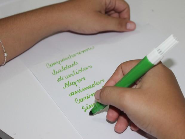 Jovem escreve no pedaço de papel qualidade das amigas (Foto: Gilcilene Araújo/G1)