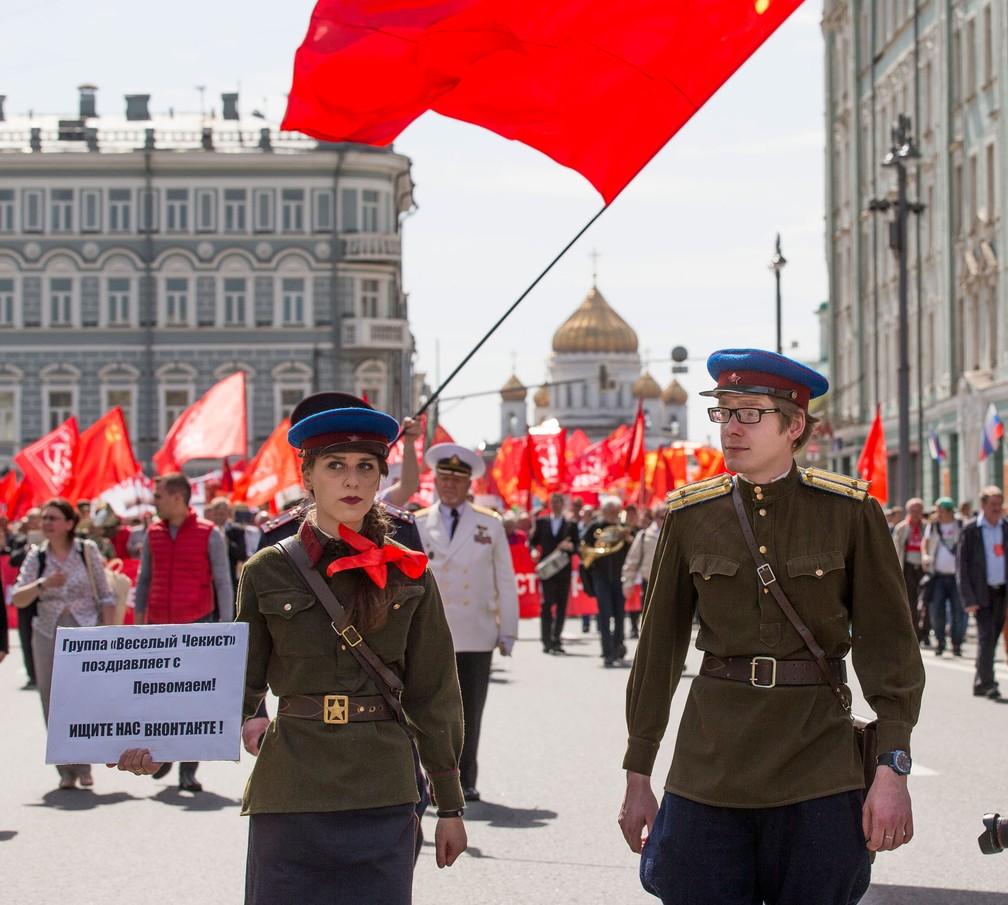 Participante de marcha do Dia do Trabalhador em Moscou usam uniforme da NKVD, nome da polícia secreta soviética entre 1934 e 1946, ao participar de marcha organizada por comunistas nesta segunda-feira, dia 1º de maio de 2017; a exemplo da época soviética, eles desfilaram com bandeiras vermelhas com o símbolo do martelo e da foice (Foto: Alexander Zemlianichenko/AP)