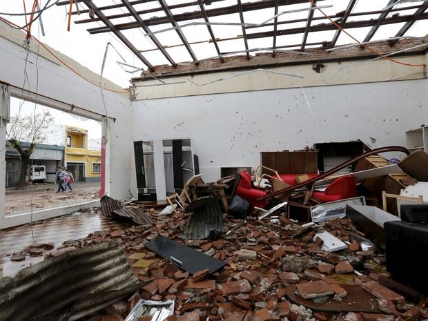 Pessoas caminham em frente a casa que teve telhado arrancado por furação em Dolores. (Foto: Reuters)